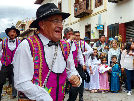 Ð¡uenca, Ecuador - December 24, 2019: Christmas parade Pase del Nino Viajero (Traveling Child). Senior man with group of dancers as participants of parade. Event is intangible heritage of UNESCO