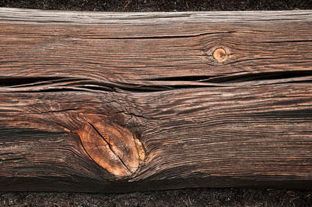 Gnarled wooden beam wall of an old building close  photo