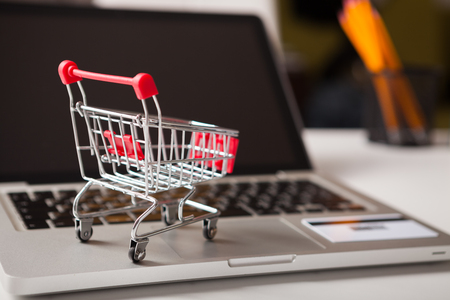 Online shopping. Bank card nearby a laptop and shopping cart on white background top view.