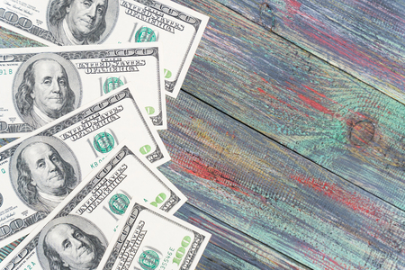 Money on a colored wooden background. Stack of one hundred dollars bills on wooden desk