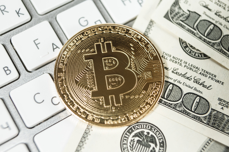 New virtual money Golden bitcoin coin and dollars on a white keyboard. Cryptocurrency. Business and Trading concept.