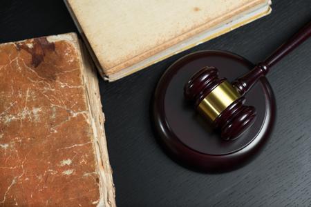 Judge gavel beside pile of books on black wooden background Stock Photo