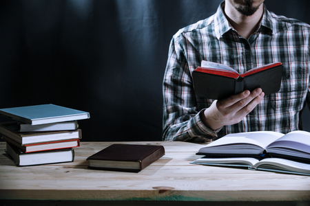 Close up of a man reading a book on the wooden table. Education concept with copy space