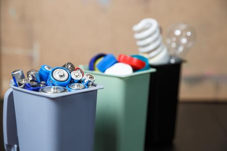 Concepto de ecología, muchos objetos reciclables en contenedores en el fondo de madera.