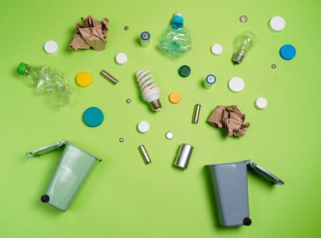 Cubos de basura y basura variada aislados en verde, concepto de reciclaje, vista superior