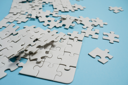 Missing jigsaw puzzle pieces. Business concept. Fragment of a folded white jigsaw puzzle and a pile of uncombed puzzle elements against the background of a blue surface. Imagens