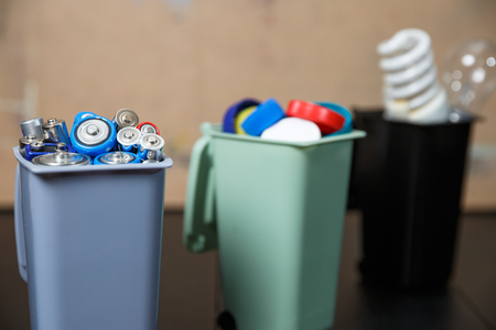 Ecology concept, a lot of recyclable objects in containers on the wooden background.