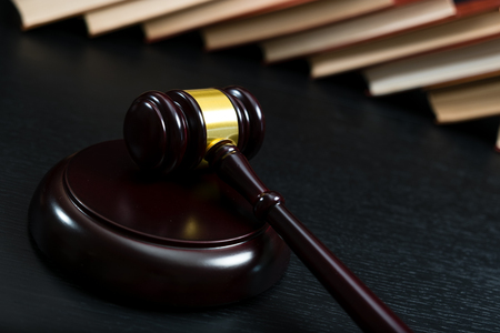 Judge gavel beside pile of books on black wooden background Banque d'images