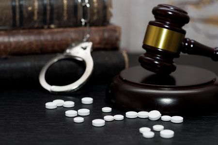 Judges gavel with handcuffs, drugs on wooden table, drugs concept