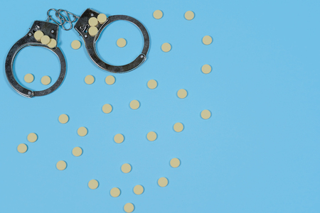 Pills on a blue background whith spoon and handcuffs. Copy spase, spase for text. Stock Photo