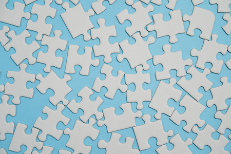 Missing jigsaw puzzle pieces. Business concept. Fragment of a folded white jigsaw puzzle and a pile of uncombed puzzle elements against the background of a blue surface. Stock Photo