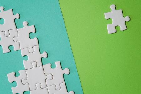Missing jigsaw puzzle pieces. Business concept. Fragment of a folded white jigsaw puzzle and a pile of uncombed puzzle elements against the background of a colored surface. Stock Photo