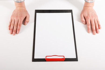 Hand holding blank clip board with white paper design mockup. Clear a4 document folder mock up template hold in arm. Clipboard notepad surface display front. Checklist tablet clamp file presentation.