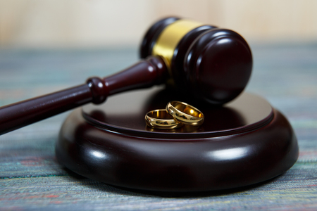 Closeup of wedding rings on wooden mallet at table in courtroom Stock Photo - 113355784