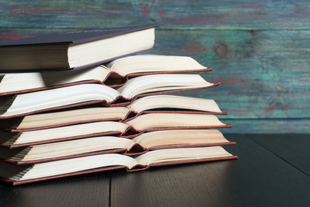 Open book hardback on Stack books on wooden background. Back to school with copy space. 写真素材