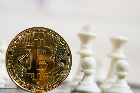 Golden bitcoin coin symbolizes elements of virtual economy or crypto currency with chess board