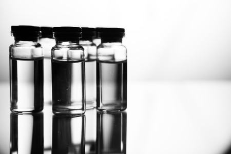 Group object of liquid medicinal agent in limpid glassware in medical laboratory. Group of ampoules with a transparent medicine in medical laboratory