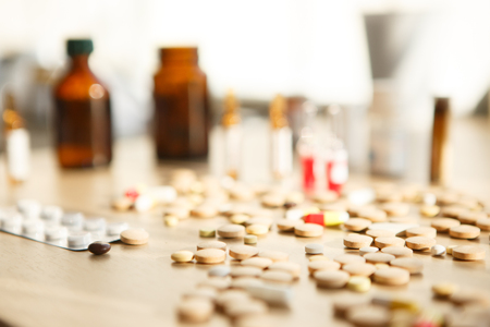 Closeup of medical capsule or pill or drug on wooden background. A lot of colorful medication and pills. Selective focus 免版税图像