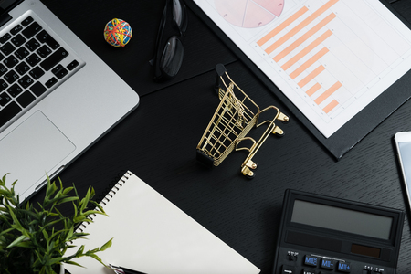 The concept of online shopping. Gold cart, cash and gadgets on a black table.