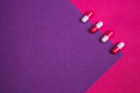 Assortment of various colourful pills on pastel coloured background. Medication and prescription pills background.