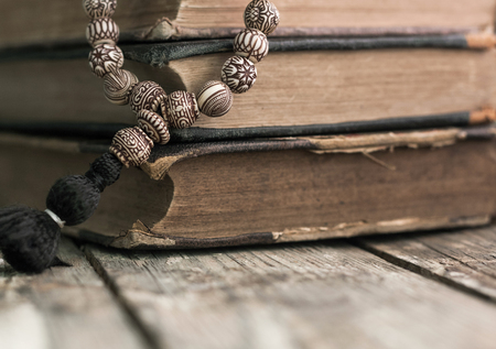 Wooden rosary beads lying on shabby battered old book lying on the old cracked wood bench with knot