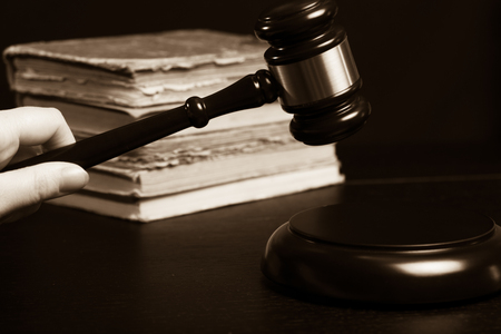 Juez martillo junto a la pila de libros sobre fondo de madera negra