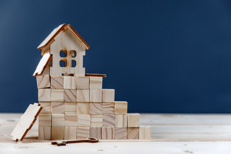 Real estate concept. Small toy wooden house with keys with copy space