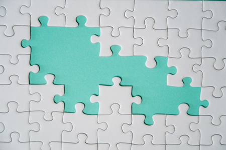 Missing jigsaw puzzle pieces. Business concept. Fragment of a folded white jigsaw puzzle and a pile of uncombed puzzle elements against the background of a colored surface. Standard-Bild - 113953280