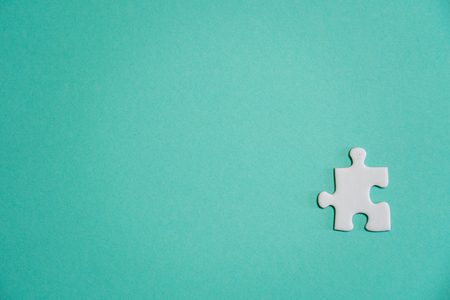 Missing jigsaw puzzle pieces. Business concept. Fragment of a folded white jigsaw puzzle and a pile of uncombed puzzle elements against the background of a colored surface. Stock fotó