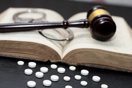 Judge's gavel with handcuffs, drugs on wooden table, drugs concept