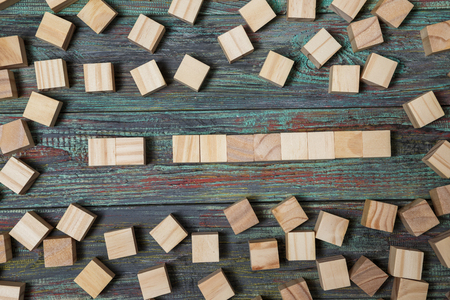 Blank wooden block leaning on a structure made of many other blocks with several of them still lying scattered on a textured rustic wooden desk. Conceptual of leisure game or start up business.