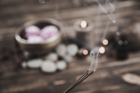 Singing bowl with candles with pebbles on dark wooden background with copy space.