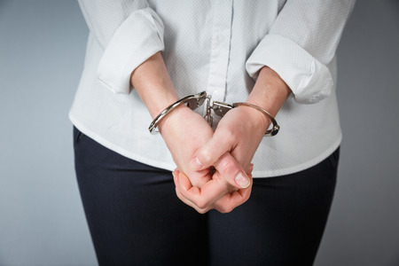 Close-up. Arrested man handcuffed hands at the back isolated on gray background. Prisoner or arrested close-up of hands in handcuffs.