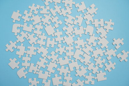 Missing jigsaw puzzle pieces. Business concept. Fragment of a folded white jigsaw puzzle and a pile of uncombed puzzle elements against the background of a blue surface. Banco de Imagens