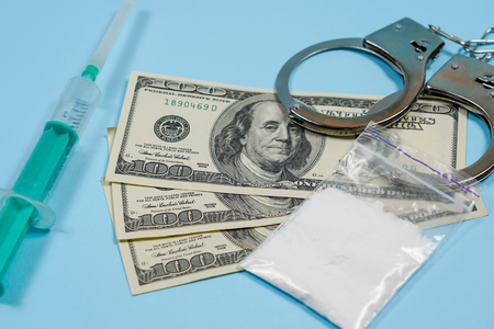 A bag of drugs, US dollars and handcuffs on the table. Concept - punishment for possession of narcotic drugs. Copy spase, spase for text.
