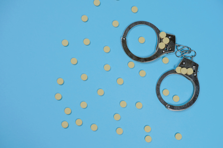 Pills on a blue background whith spoon and handcuffs. Copy spase, spase for text. Imagens
