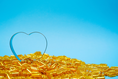 Heart shaped of gold pills on blue paper background. Copy space for text
