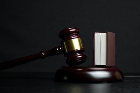 Judge gavel beside book on black wooden background
