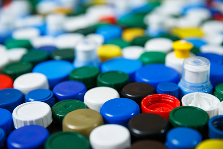 Conception of plastic processing for ecology or charity. Collection of various colorful plastic screw caps. Useful as background