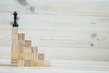 Geschäftshierarchie. Strategiekonzept mit Schachfiguren. Schach steht auf einer Pyramide aus Holzbausteinen mit dem König an der Spitze. Platz kopieren. Standard-Bild