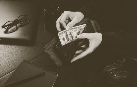Businesswoman's hand in suit takes out dollar money from a wallet. Banknote One hundred dollar. The concept of finance. Close-up. Copy space. for your background.