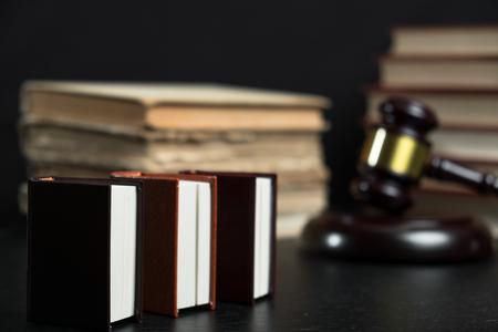 Judge gavel beside pile of books on black wooden background Stockfoto