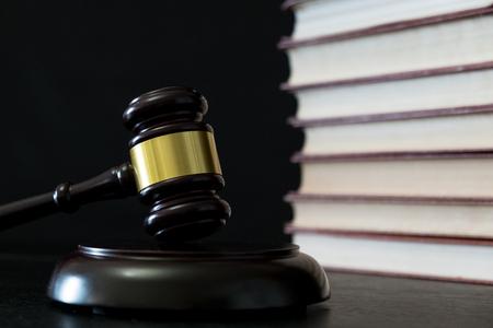Judge gavel beside pile of books on black wooden background Imagens