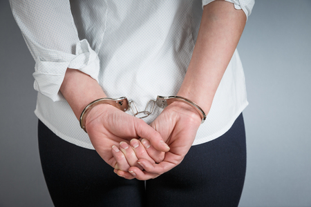 Close-up. Arrested man handcuffed hands at the back isolated on gray background. Prisoner or arrested close-up of hands in handcuffs. Stock Photo - 118168939