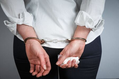 Handcuffed female hands holding a bag of drugs. Drug trafficking concept