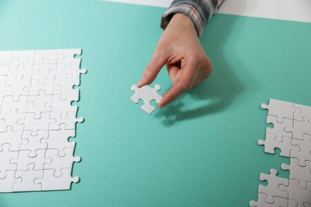 Hands assembling jigsaw puzzle, to find common solution concept Stock Photo
