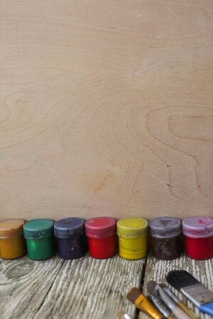 Different colorful brushes on the table, wooden background. Clean painter workplace ready for drawing. with copy space