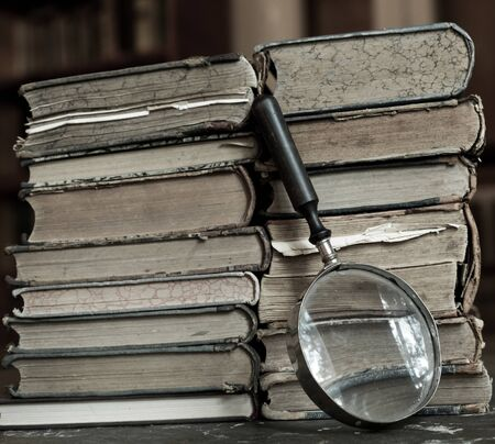 Antique books with magnifying glass. Old leather bound vintage books in a row