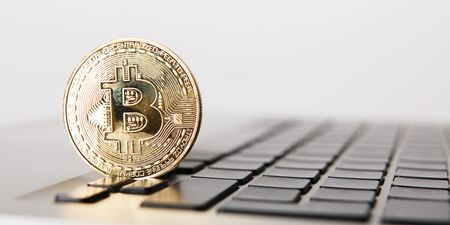 Golden Bitcoin - New virtual money on notebook. A visual representation of digital cryptocurrencies. Bitcoin are fully dematerialized and decentralized electronic currencies. Shallow depth of field. Stok Fotoğraf