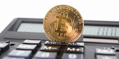 Bitcoin on the keyboard of the calculator. Shallow depth of field. A visual representation of digital cryptocurrencies. Bitcoin are fully dematerialized and decentralized electronic currencies